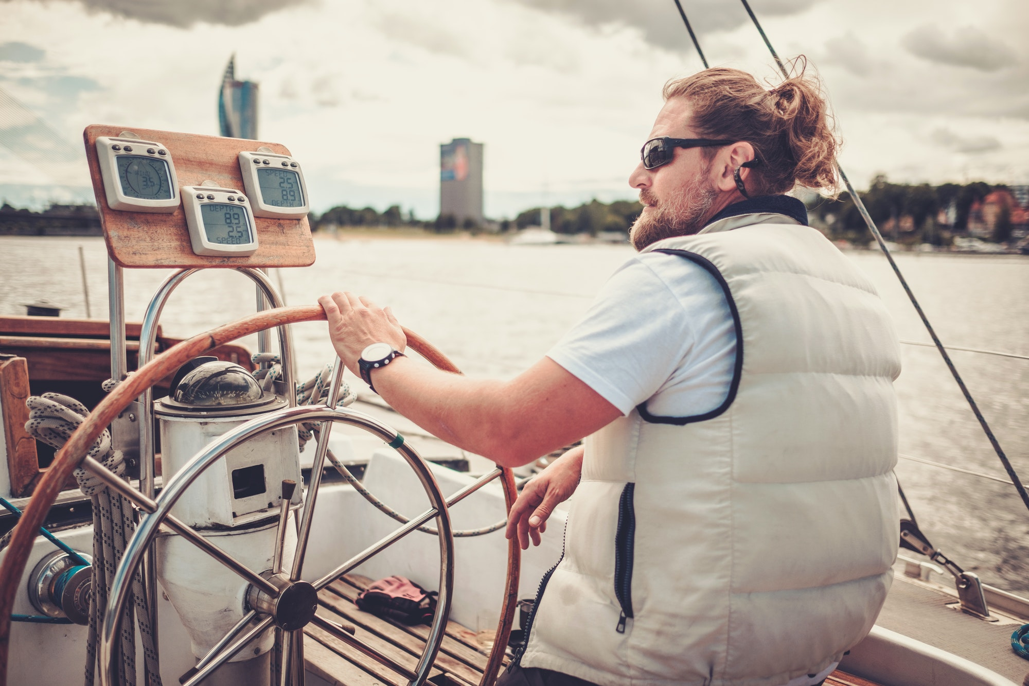 Captain on a yacht behind steering wheel